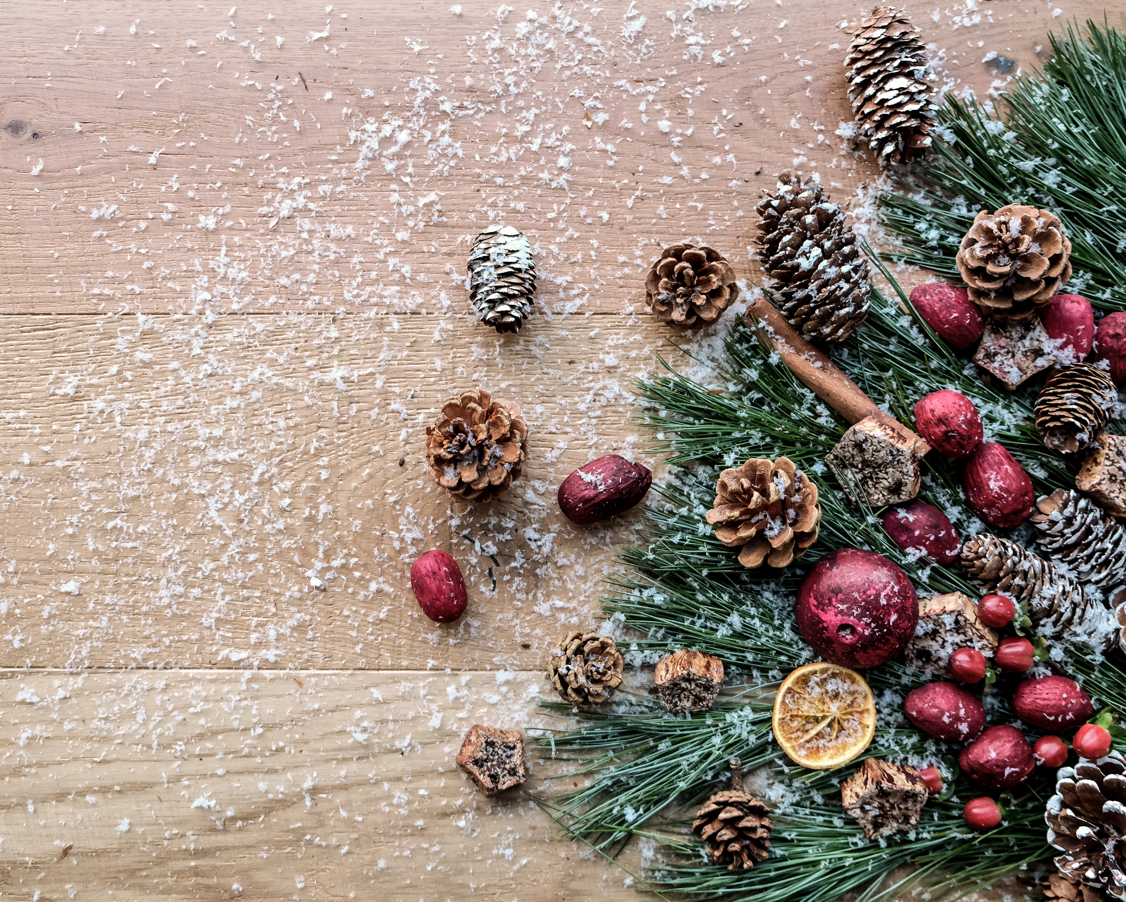 Metropolitan Hardwood Floors Christmas holiday image Kentwood flatlay- Pinecones, Pine tree branches, holly berries and snow